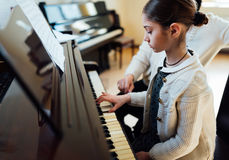 Profesor de música con el alumno en el piano de la lección Imagen de archivo libre de regalías