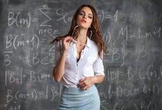 Profesor de sexo femenino atractivo joven cerca de la pizarra en actitud sexual imagen de archivo