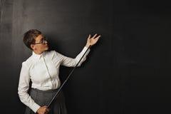 Profesor de sexo femenino con el indicador en la pizarra Imágenes de archivo libres de regalías