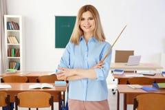 Profesor de sexo femenino con el indicador que se coloca en sala de clase Fotos de archivo