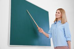 Profesor de sexo femenino con la pizarra derecha del indicador Imagenes de archivo