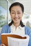 Profesor de sexo femenino Holding Book Imagenes de archivo