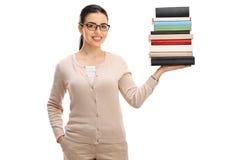 Profesor de sexo femenino joven con una pila de libros Imagenes de archivo