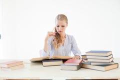 Profesor de sexo femenino que se sienta en una tabla de oficina de muchos libros Imagen de archivo libre de regalías