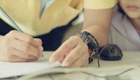 Profesor de sexo masculino en clase que circunda, la ayuda y el che de la camisa amarilla fotografía de archivo libre de regalías