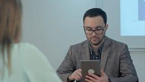 Profesor de sexo masculino en el sitio de clase que da el tema que usa la tableta Foto de archivo libre de regalías