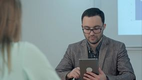Profesor de sexo masculino en el sitio de clase que da el tema que usa la tableta Imagen de archivo libre de regalías
