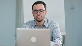 Profesor de sexo masculino hermoso en vidrios que mecanografía en el ordenador portátil Imágenes de archivo libres de regalías