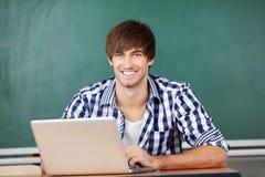 Profesor de sexo masculino With Laptop Sitting en el escritorio contra la pizarra Imagenes de archivo