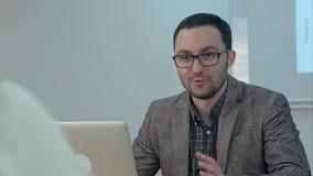 Profesor de sexo masculino positivo que mecanografía en un ordenador portátil que se sienta en una tabla y una charla a la clase Foto de archivo
