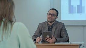 Profesor de sexo masculino profesional que explica las ideas principales del ensayo que hacen la discusión entre los estudiantes  Imágenes de archivo libres de regalías