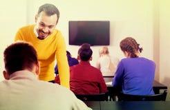 Profesor de sexo masculino que aclara el problema complicado al alumno durante examen Foto de archivo