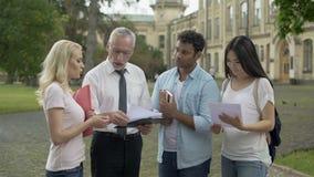 Profesor de sexo masculino que da pruebas a los estudiantes multi-étnicos y que explica resultados almacen de video