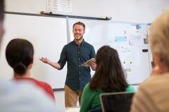 Profesor de sexo masculino que escucha los estudiantes en la clase de la enseñanza para adultos imágenes de archivo libres de regalías