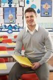 Profesor de sexo masculino que se sienta en el escritorio en sala de clase Foto de archivo libre de regalías