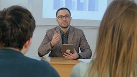 Profesor de sexo masculino que sostiene una tableta que se sienta delante de clase Imagen de archivo libre de regalías