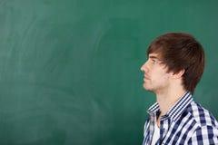 Profesor de sexo masculino Thinking In Front Of Chalkboard Foto de archivo libre de regalías