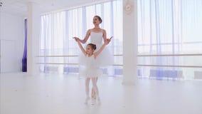 Profesor del ballet con pasos del entrenamiento de la niña de puntillas en manos del control de los pointes almacen de video