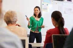 Profesor delante de estudiantes en una clase de la enseñanza para adultos Fotografía de archivo libre de regalías