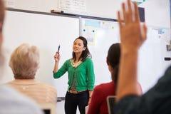 Profesor delante de estudiantes en una clase de la enseñanza para adultos Imágenes de archivo libres de regalías
