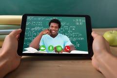Profesor On Digital Tablet de Video Conferencing With del estudiante imagen de archivo libre de regalías