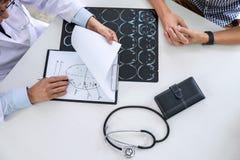 Profesor Doctor que tiene conversación con el paciente y que sostiene la película de radiografía mientras que discute explicando  fotos de archivo
