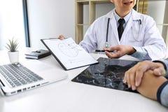 Profesor Doctor que tiene conversación con el paciente y que sostiene la película de radiografía mientras que discute explicando  imagen de archivo libre de regalías