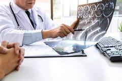 Profesor Doctor que tiene conversación con el paciente y que sostiene la película de radiografía mientras que discute explicando  foto de archivo
