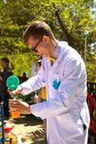 Profesor elegante joven que realiza un experimento en la demostración de la ciencia para los niños Foto de archivo
