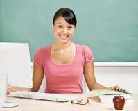 Profesor en el escritorio en sala de clase Fotos de archivo libres de regalías