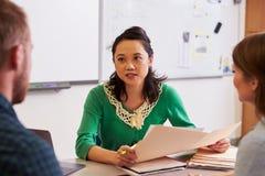 Profesor en el escritorio que habla con los estudiantes de la enseñanza para adultos Fotografía de archivo