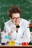 Profesor enojado rodeado con cristalería química Fotos de archivo libres de regalías