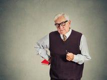 Profesor estricto mayor serio que sostiene el libro y la pluma fotos de archivo libres de regalías