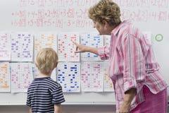 Profesor Explaining Calendar To Little Boy Imagen de archivo