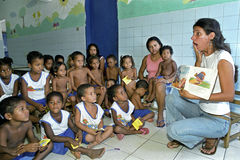 Profesor expresivo que lee para los niños Fotos de archivo libres de regalías