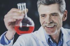 Profesor feliz Look en el frasco con el líquido químico imágenes de archivo libres de regalías