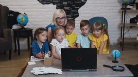 Profesor feliz que usa el ordenador portátil con los alumnos en la sala de clase de la geografía Profesor que ayuda a los niños c metrajes