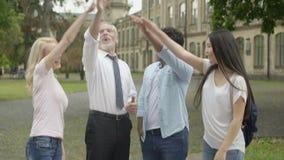 Profesor feliz y estudiantes multirraciales que ponen las manos en la pila, formación de equipo almacen de metraje de vídeo