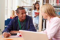 Profesor Helping College Student con estudios en biblioteca Foto de archivo