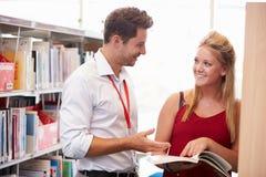 Profesor Helping College Student con estudios en biblioteca Foto de archivo libre de regalías