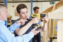 Profesor Helping College Student que estudia la carpintería Imagen de archivo libre de regalías