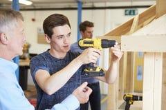 Profesor Helping College Student que estudia la carpintería Imagenes de archivo