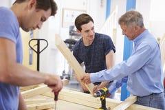 Profesor Helping College Student que estudia la carpintería Foto de archivo libre de regalías