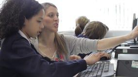Profesor Helping Female Pupil en clase del ordenador almacen de metraje de vídeo