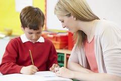 Profesor Helping Male Pupil con la escritura practicante en el escritorio Foto de archivo libre de regalías