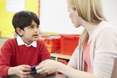Profesor Helping Male Pupil con matemáticas en el escritorio Foto de archivo libre de regalías