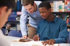 Profesor Helping Male Student en sala de clase Imagenes de archivo