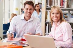 Profesor Helping Mature Student con estudios en biblioteca Foto de archivo