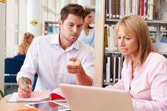 Profesor Helping Mature Student con estudios en biblioteca Foto de archivo libre de regalías