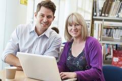 Profesor Helping Mature Student con estudios en biblioteca Imágenes de archivo libres de regalías